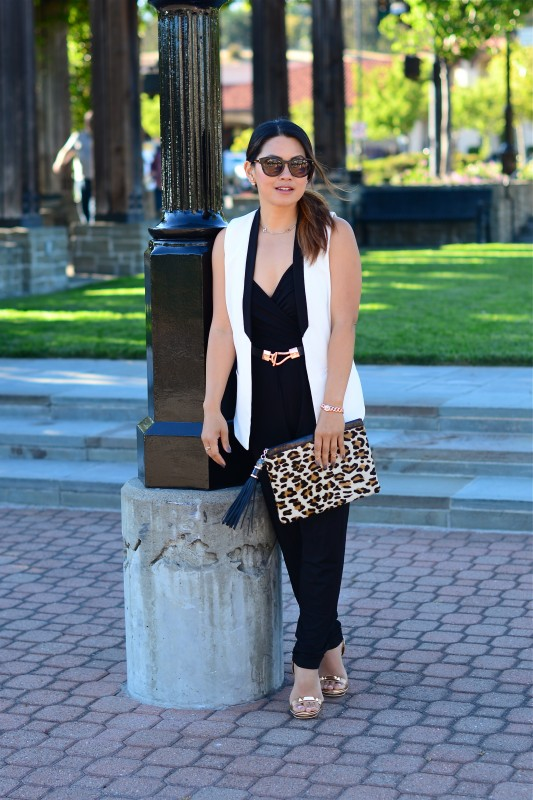 Stylish black jumpsuit and sleeveless blazer and leopard clutch