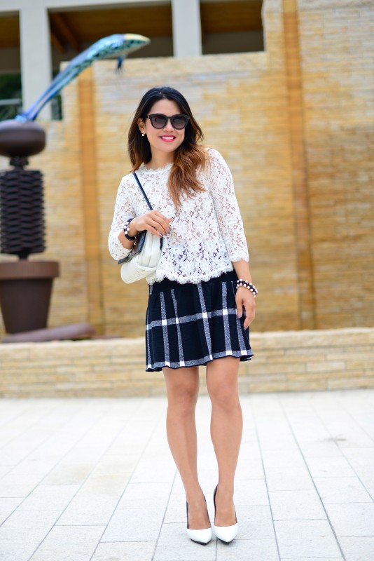 Chic black and white outfit in lace long sleeve top and flared plaid skirt