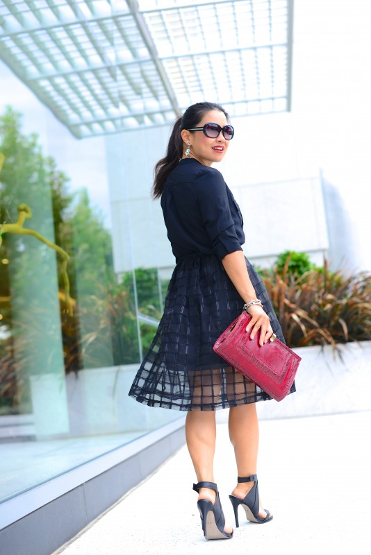 Business outfit in sheer midi skirt and silk blouse and red clutch